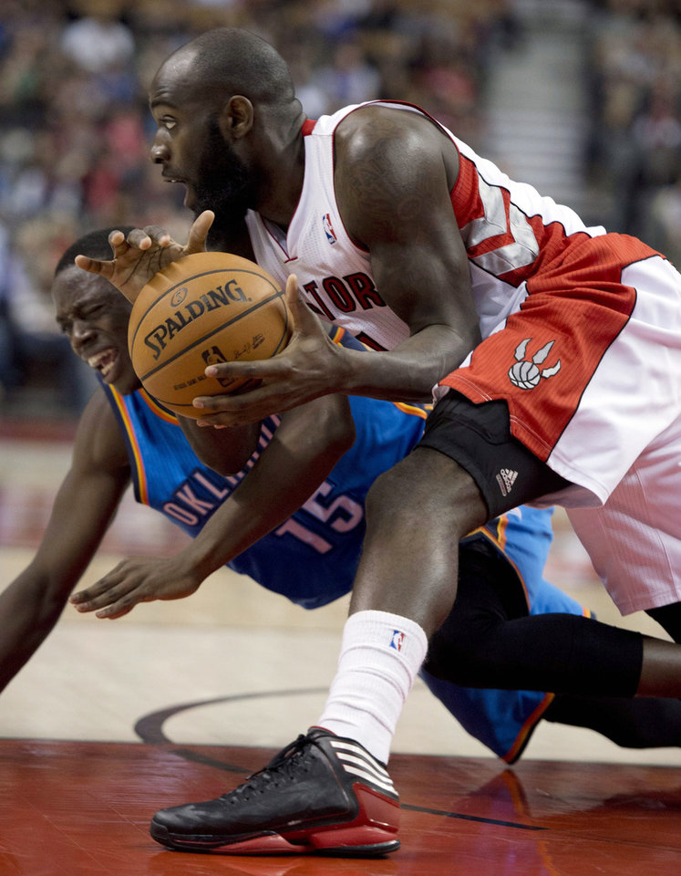 Toronto Raptors forward Quincy Acy, right, and Oklahoma City Thunder guard Reggie Jackson (15) dive for a loose ball during the second half of an NBA basketball game in Toronto on Sunday, Jan. 6, 2013. (AP Photo/The Canadian Press, Frank Gunn) ORG XMIT: FNG111