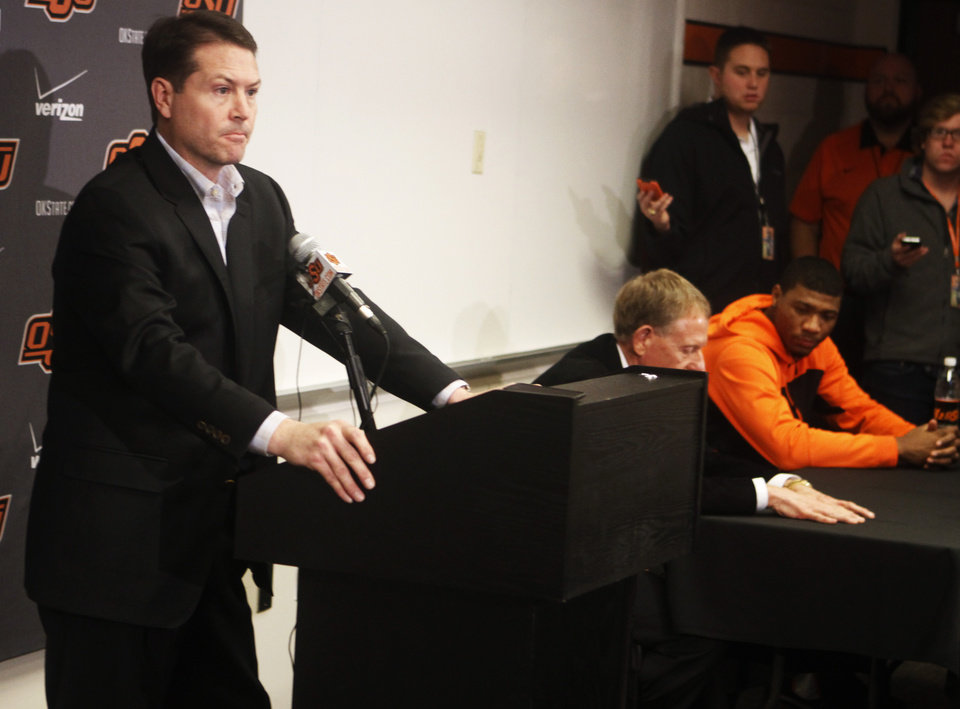 Photo - Oklahoma State basketball coach Travis Ford addresses media members at a press conference held in Gallagher Iba Arena on Sunday, Feb. 9, 2014 while Oklahoma State athletic director Mike Holder and basketball player Marcus Smart look on. The press conference was held the day after star player Marcus Smart shoved a fan during an altercation in a game Saturday, Feb. 8, 2014. Smart was given a three game suspension by the Big 12 conference and Oklahoma State. Photo by KT King/The Oklahoman