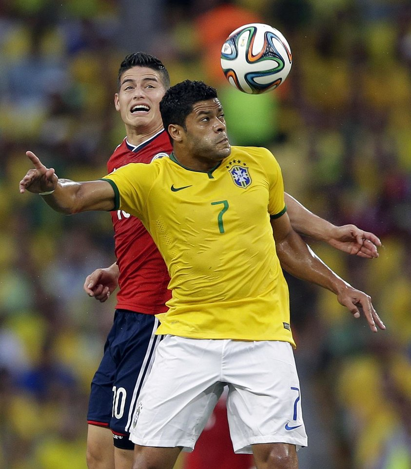 Photo - Colombia's James Rodriguez tries to head the ball against Brazil's Hulk during the World Cup quarterfinal soccer match between Brazil and Colombia at the Arena Castelao in Fortaleza, Brazil, Friday, July 4, 2014. (AP Photo/Andre Penner)