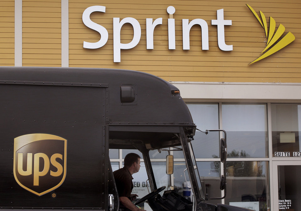 FILE - In this Thursday, July 19, 2012 file photo, a UPS truck stops in front of a Sprint store at the Derby Street Shoppes in Hingham, Mass. Sprint Nextel Corp. reports quarterly financial results before the market opens on Wednesday, April 24, 2013 (AP Photo/Stephan Savoia)