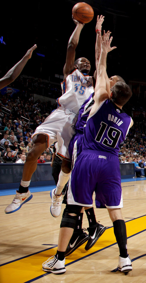 Photo - Oklahoma City's Kevin Durant puts up a shot over Sacramento's Beno Idrih, right, and Francisco Garcia during the NBA basketball game between the Oklahoma City Thunder and the Sacramento Kings at the Ford Center in Oklahoma City, Tuesday, March 2, 2010.  Photo by Bryan Terry, The Oklahoman