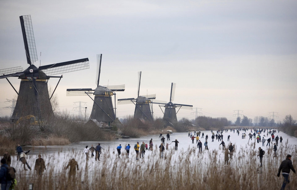 Photo - FILE - In this Jan. 3, 2009, file photo, people skate on frozen canals in Kinderdijk's Mill Area, near Rotterdam, Netherlands. There is nothing more mythical in Dutch sports than an age-old 11-city race skating across lakes and canals in bone-numbing cold from dawn to dusk. No wonder the Netherlands is the greatest speedskating nation in the world. And with Sven Kramer and Ireen Wust leading the way on big oval in Sochi they are bent on proving it again.  (AP Photo/Peter Dejong, File)