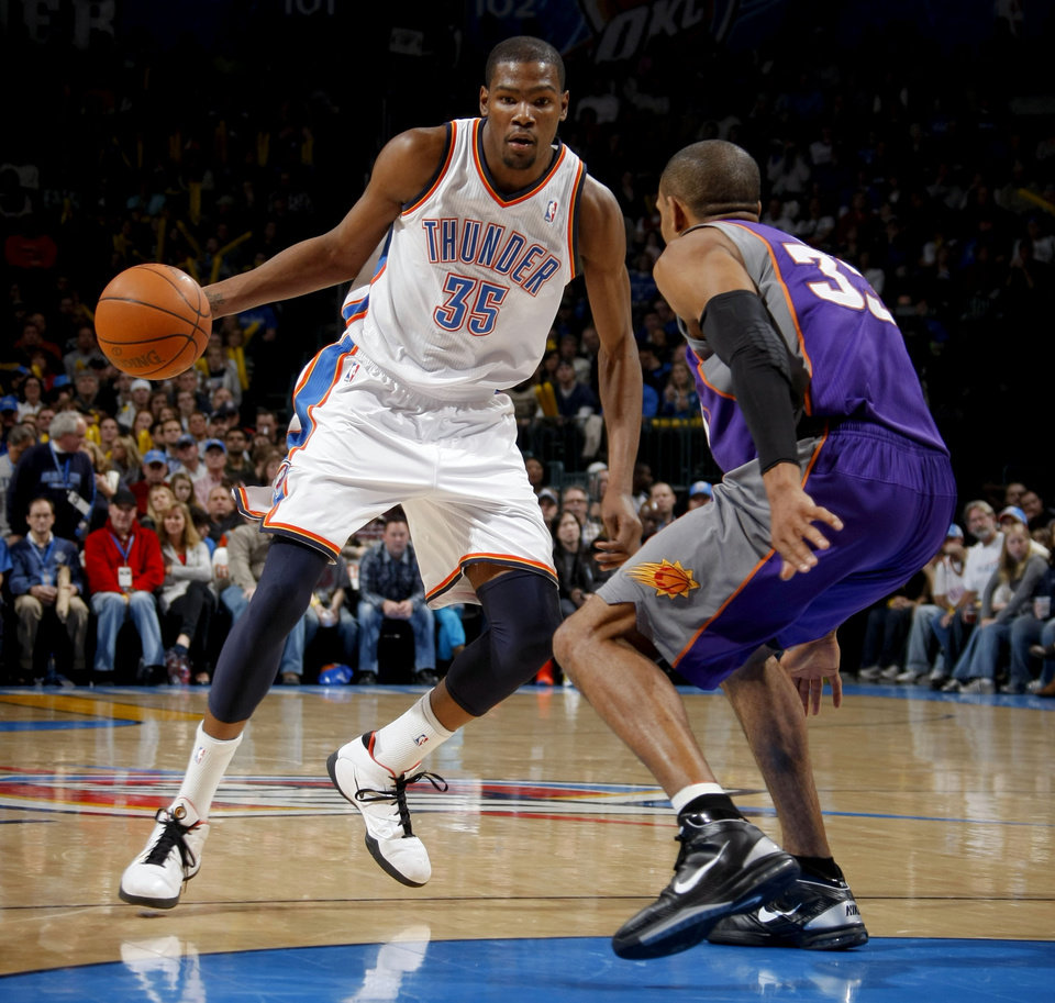 Photo - Oklahoma City's Kevin Durant (35) tries to get by Phoenix's Grant Hill (33) during the NBA basketball game between the Oklahoma City Thunder and the Phoenix Suns, Sunday, Dec. 19, 2010, at the Oklahoma City Arena. Photo by Sarah Phipps, The Oklahoman