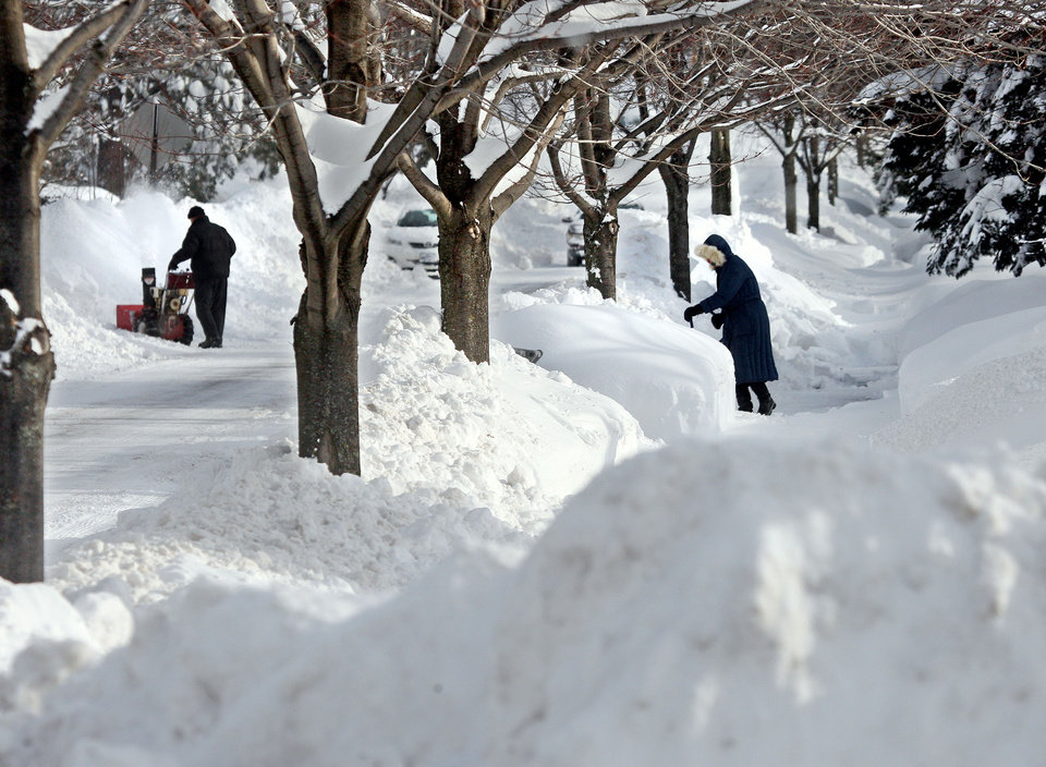Wayne Neally runs a snowblower to clear his driveway while Deanne Ferguson does her clearing the old-fashioned way with a large snow scoop, right, Thursday, Dec. 5, 2013. Ferguson's would have preferred a snowblower, but hers broke yesterday. (AP Photo/Duluth News Tribune, Bob King)