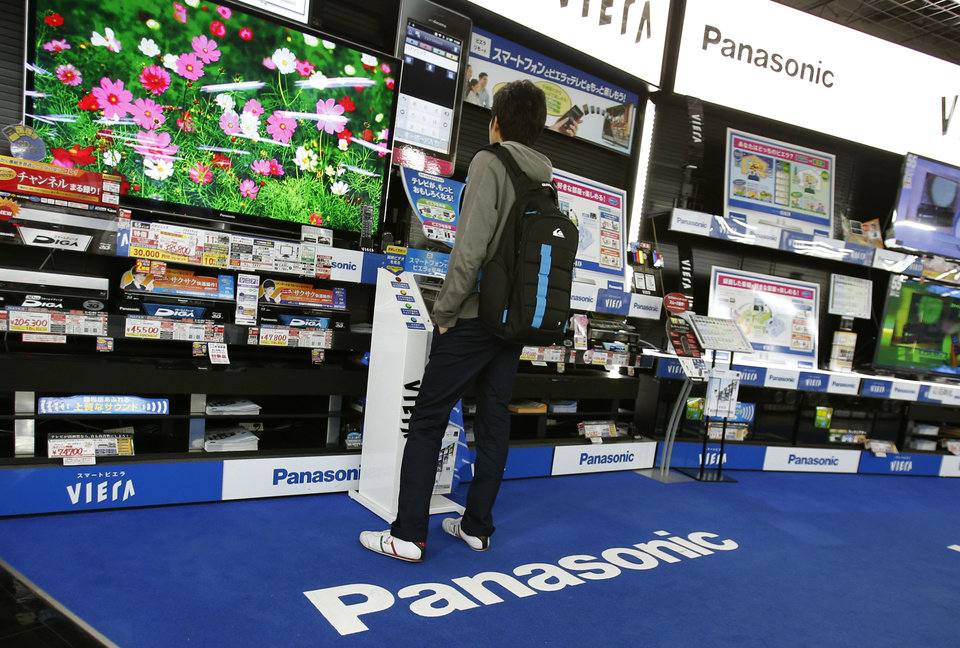 Photo - A shopper looks at a Panasonic flat-panel television at an electronics retail store in Tokyo Thursday, March 28, 2013. Panasonic Corp.'s president said Thursday the company will get out of unprofitable businesses but stopped short of ditching the Japanese manufacturer's money-losing TV operations, as had been widely speculated. (AP Photo/Shizuo Kambayashi)