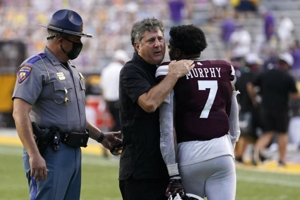 Photo -  Mississippi State coach Mike Leach hugs safety Marcus Murphy (7) after the Bulldogs beat LSU 44-34 Saturday in Baton Rouge, La. [AP Photo/Gerald Herbert]