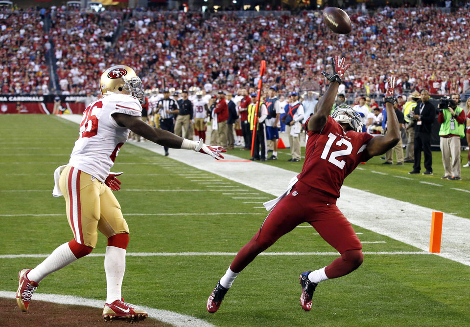 Arizona Cardinals wide receiver Andre Roberts (12) pulls in a touchdown pass as San Francisco 49ers cornerback Tramaine Brock defends during the second half of an NFL football game, Sunday, Dec. 29, 2013, in Glendale, Ariz.  (AP Photo/Ross D. Franklin)