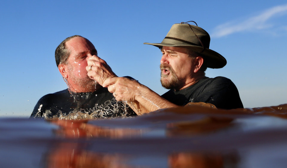 Photo -  The Rev. Dave Evans with Highland Park Baptist Church baptizes Dr. Brian Johnson   at Clear Bay Point at Lake Thunderbird, Sunday, June 28, 2015, in Norman, Okla. Photo by Sarah Phipps, The Oklahoman