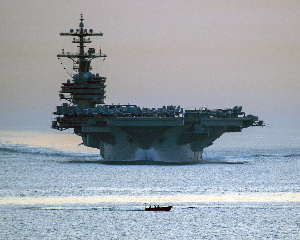 Photo - This image provided by the U.S. Navy shows a small vessel transiting in front of the aircraft carrier USS George H.W. Bush as it transits the Strait of Hormuz April 28, 2014 as seen from the guided-missile cruiser USS Philippine Sea. Defense Secretary Chuck Hagel ordered the USS George H.W. Bush from the northern Arabian Sea Saturday June 14, 2014 as President Barack Obama considered possible military options for Iraq. (AP Photo/US Navy, Specialist 3rd Class Abe McNatt)