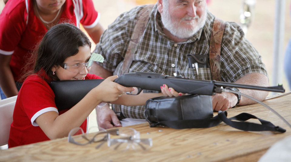 Photo - Ten year old Stacy Mares shoots an air rifle during school day of the Oklahoma Wildlife Expo at the Lazy E Arena and Ranch in Guthrie, OK, Friday, September 28, 2012,  By Paul Hellstern, The Oklahoman