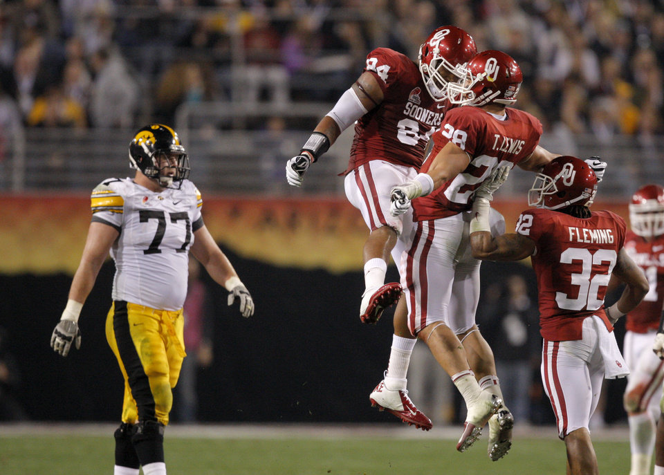 Photo - Oklahoma's Frank Alexander (84), Travis Lewis (28) and Jamell Fleming (32) celebrate in front  of  Iowa's Riley Reiff (77) during the Insight Bowl college football game between the University of Oklahoma (OU) Sooners and the Iowa Hawkeyes at Sun Devil Stadium in Tempe, Ariz., Friday, Dec. 30, 2011. Photo by Sarah Phipps, The Oklahoman