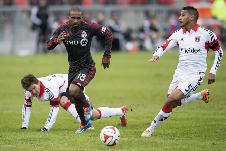 Toronto FC \'s Jermain Defoe (18) drives between D.C. United\'s Bobby Boswell, left, and Sean Franklin during the second half of an MLS soccer game in Toronto on Saturday, March 22, 2014. (AP Photo/The Canadian Press, Chris Young)
