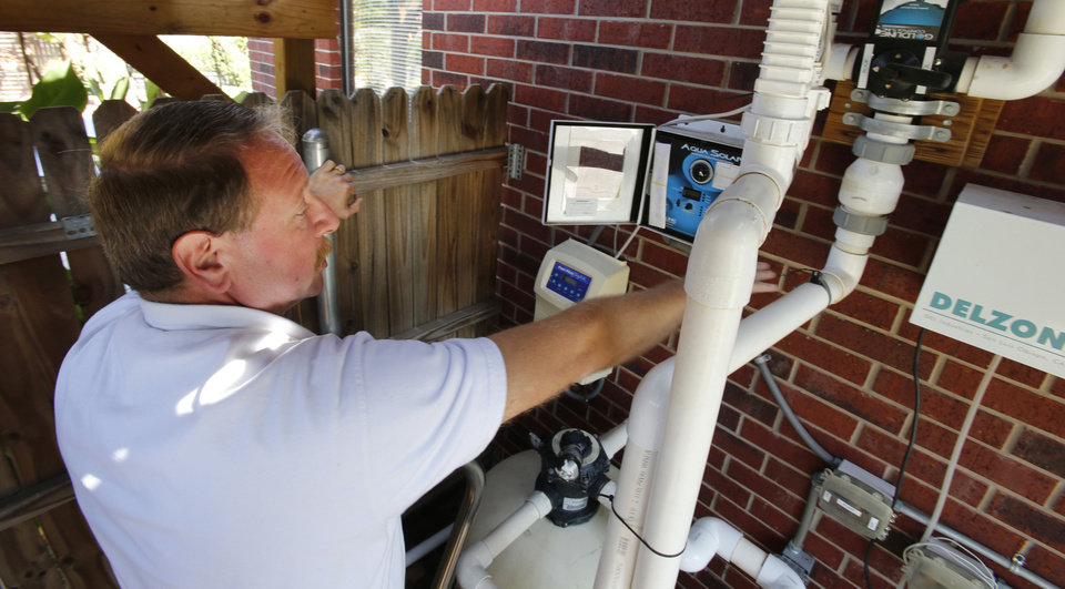 Photo - Choctaw resident Jim Stober shows alternative energy sources including the thermal heating system for his pool at his home.  Photo by Steve Sisney, The Oklahoman  STEVE SISNEY - THE OKLAHOMAN