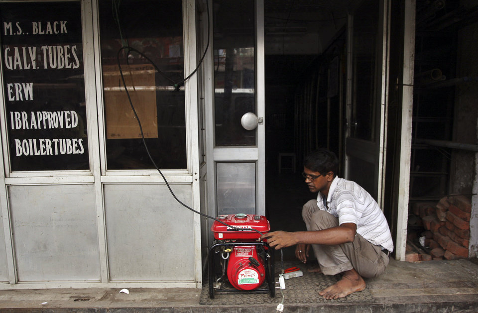 Photo -   An Indian shopkeeper fixes an electric generator at his shop in New Delhi, India, Tuesday, July 31, 2012. India's energy crisis cascaded over half the country Tuesday when three of its regional grids collapsed, leaving 620 million people without government-supplied electricity in one of the world's biggest-ever blackouts. (AP Photo/Tsering Topgyal)