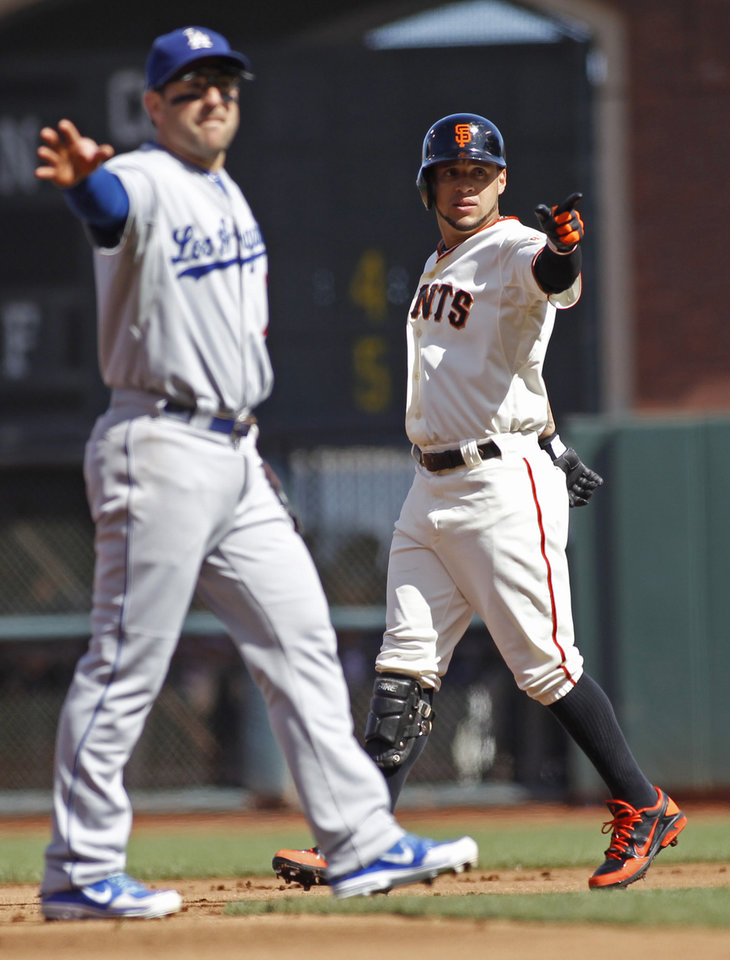 Photo - San Francisco Giants' Gregor Blanco, right, reacts after hitting a double against the Los Angeles Dodgers during the first inning of a baseball game in San Francisco, Saturday, July 6, 2013. Dodgers Nick Punto, left, looks on. (AP Photo/George Nikitin)