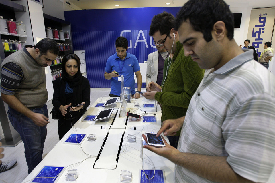 Photo -   Potential customers try out Samsung cell phones and tablet computers in a store, in Tehran, Iran, Thursday, Nov. 8, 2012. Sanctions-hit Iran has banned the import of foreign-made cars, laptops, and other 'luxury' goods in the hope of saving billions of dollars in hard currency, a state-owned newspaper reported Thursday. IRAN daily listed 75 products, from watches, home appliances and cell phones to coffee and toilet paper, that it said could no longer be purchased from abroad. But it says the ban does not apply to components used to produce the products. Iranian firms assemble many products including watches, laptops and cell phones. (AP Photo/Vahid Salemi)