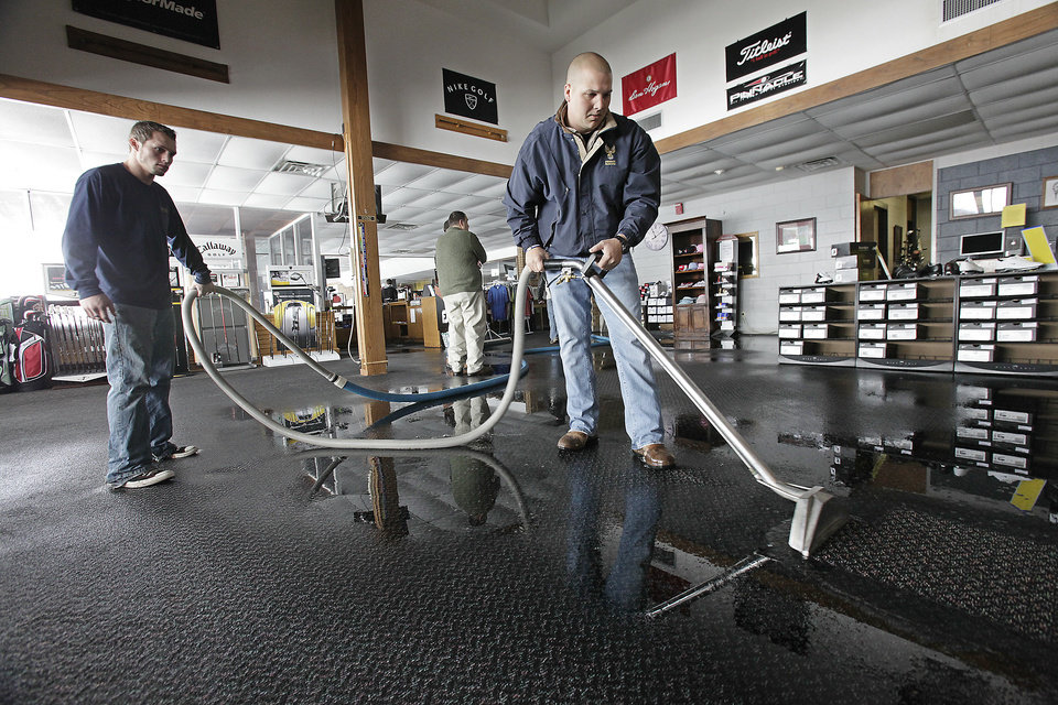 Photo - Jeff Bleything with Phoenix Restoration Services vacuums up water in pro shop at KickingBird golf course in Edmond, Wednesday, February 2, 2011.   The water line broke due to the cold weather.       Photo by David McDaniel, The Oklahoman