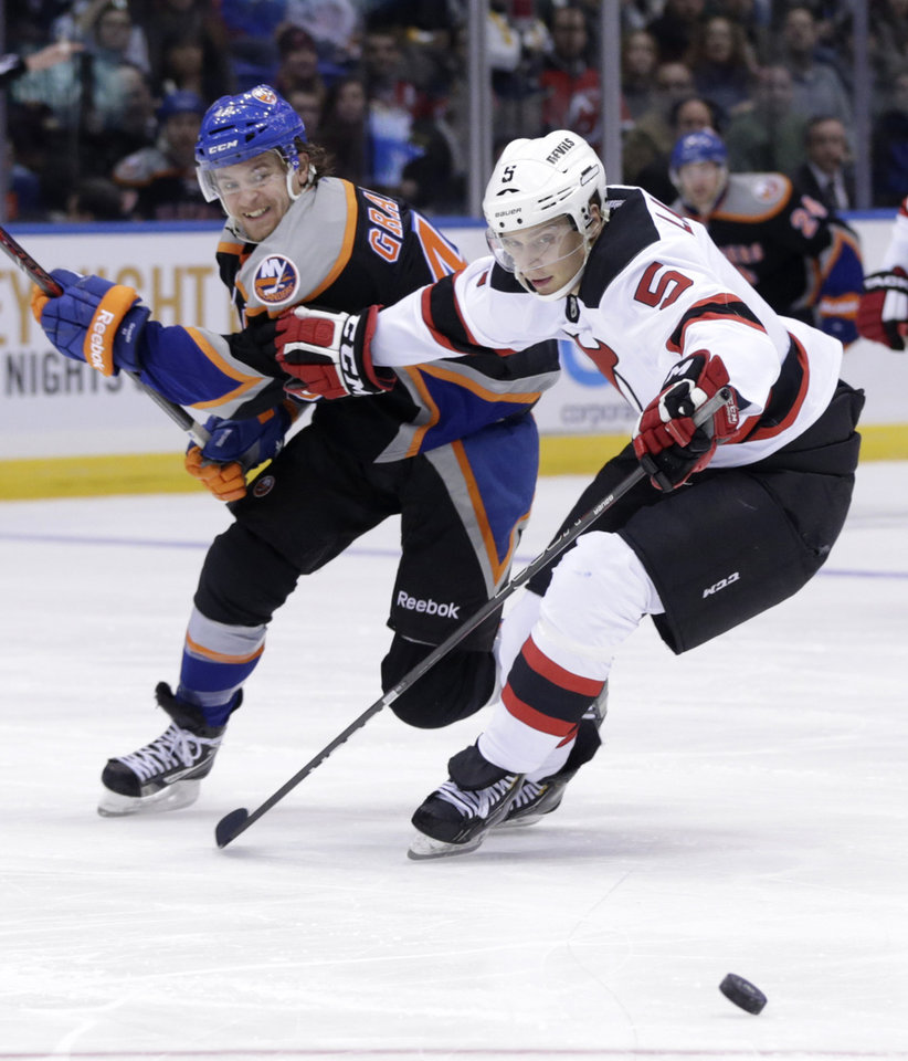 Photo - New Jersey Devils' Adam Larsson, right, battles for the puck with New York Islanders' Michael Grabner during the second period of the NHL hockey game on Sunday, Feb. 3, 2013, in Uniondale, N.Y. (AP Photo/Seth Wenig)