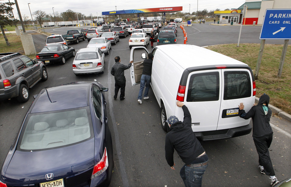 People help push John Oh\'s van to the pumps at the New Jersey Turnpike\'s Thomas A. Edison service area Wednesday, Oct. 31, 2012, near Woodbridge, N.J., after Oh, of Blue Bell, Pa., ran out of gas waiting in a long line near exit 11. After Monday\'s storm surge from Sandy, many gas stations in the region are without power and those that are open have very long lines. (AP Photo/Mel Evans) ORG XMIT: NJME109