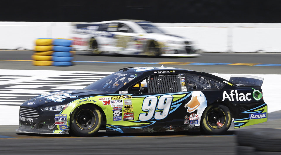Photo - Carl Edwards (99) races, with Dale Earnhardt Jr. in the background, during the NASCAR Sprint Cup Series auto race Sunday, June 22, 2014, in Sonoma, Calif. Edwards won the race and Earnhardt finished third. (AP Photo/Eric Risberg)