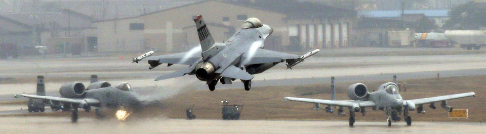 Photo - A U.S. Air Force F-16 fighter jet, center, lands on the runway during their military exercise at the Osan U.S. Air Base in Pyeongtaek, south of Seoul, South Korea, Tuesday, April 2, 2013. North Korea vowed Tuesday to restart a nuclear reactor that can make one bomb's worth of plutonium a year, escalating tensions already raised by near daily warlike threats against the United States and South Korea. (AP Photo/Bae Jung-hyun, Yonhap) KOREA OUT