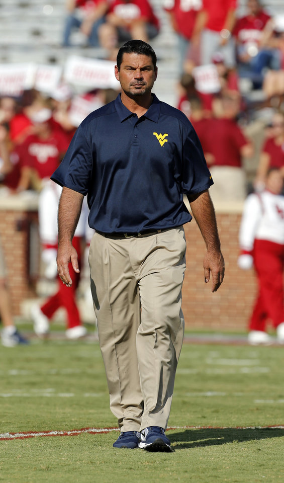Photo - West Virginia special teams coach Joe DeForest walks on the field before a college football game between the University of Oklahoma Sooners (OU) and the West Virginia University Mountaineers at Gaylord Family-Oklahoma Memorial Stadium in Norman, Okla., on Saturday, Sept. 7, 2013. Photo by Steve Sisney, The Oklahoman