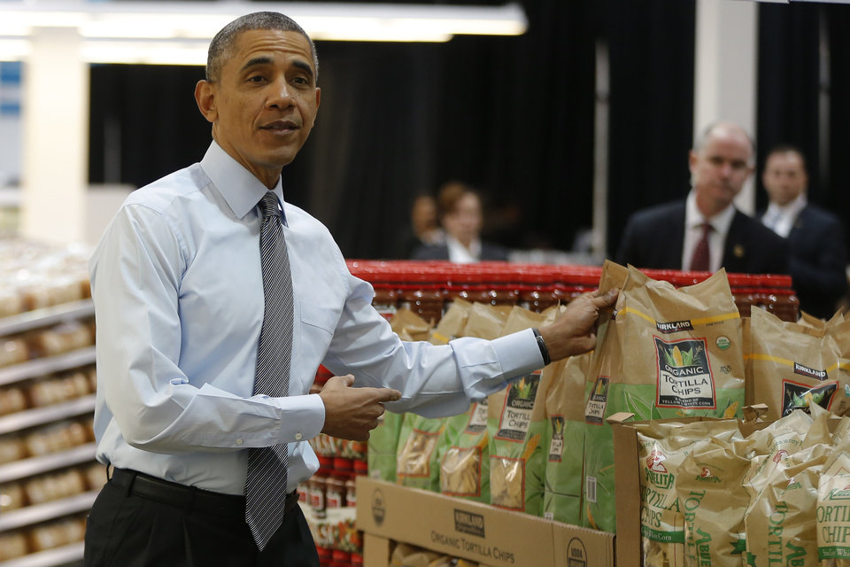 Photo - President Barack Obama holds up a bag of tortilla chips during a visit at a Costco store in Lanham, Md., Wednesday, Jan. 29, 2014, where he spoke about raising the minimum wage the morning after his State of the Union address.  (AP Photo/Charles Dharapak)