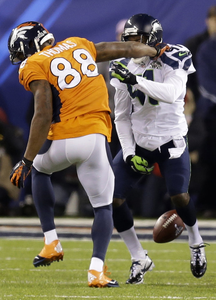 Photo - Denver Broncos' Demaryius Thomas, left, fumbles the ball as he his hit by Seattle Seahawks' Byron Maxwell during the second half of the NFL Super Bowl XLVIII football game Sunday, Feb. 2, 2014, in East Rutherford, N.J. (AP Photo/Ben Margot)