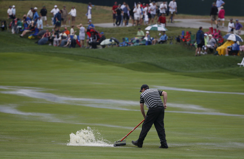 Photo - A course worker push rain water off the first hole during a weather delay in final round of the PGA Championship golf tournament at Valhalla Golf Club on Sunday, Aug. 10, 2014, in Louisville, Ky. (AP Photo/Mike Groll)