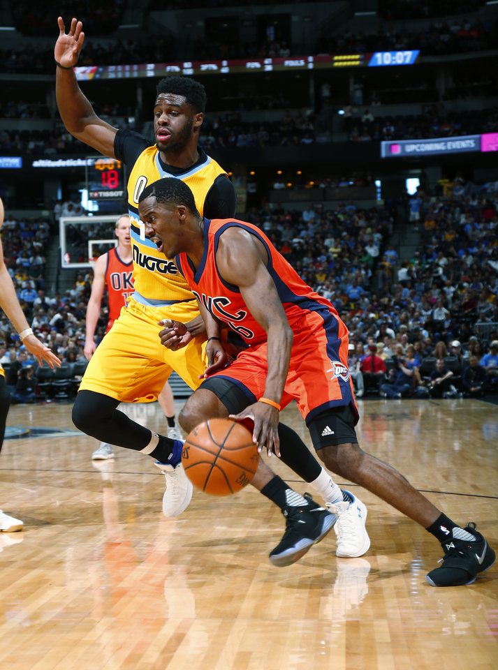 Photo - Oklahoma City Thunder guard Semaj Christon (6) drives past Denver Nuggets guard Emmanuel Mudiay (0) during the first half of a basketball game, Sunday, April 9, 2017, in Denver. (AP Photo/Jack Dempsey)