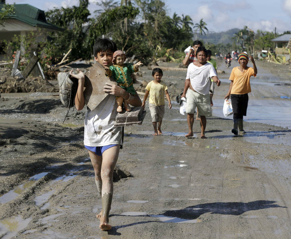 Residents, impacted by Tuesday's storm,  walk back to an evacuation center after retrieving their household items, including religious images, Thursday, Dec. 6, 2012, in New Bataan township, Compostela Valley in the southern Philippines. The powerful typhoon that washed away emergency shelters, a military camp and possibly entire families in the southern Philippines has killed hundreds of people with nearly 400 missing, authorities said Thursday. (AP Photo/Bullit Marquez)