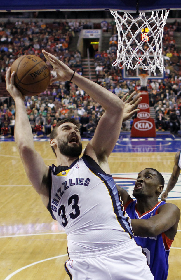Photo - Memphis Grizzlies' Marc Gasol, left, of Spain, goes up for a shot against Philadelphia 76ers' Jarvis Varnado during the first half of an NBA basketball game, Saturday, March 15, 2014, in Philadelphia. (AP Photo/Matt Slocum)