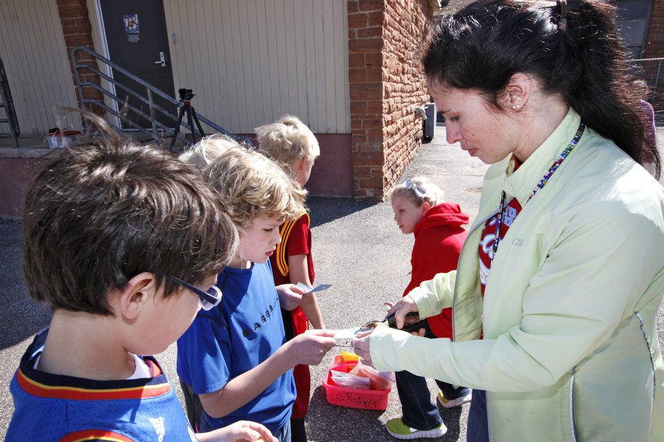 Left: Second-graders Jack Ray and Stratton White get their lap tickets punched by Joann Imes on Friday while running laps around the playground during recess. Students at Russell Doughtery Elementary School, in Edmond, are preparing for the Kids Memorial Marathon. Photo By David McDaniel,  The Oklahoman