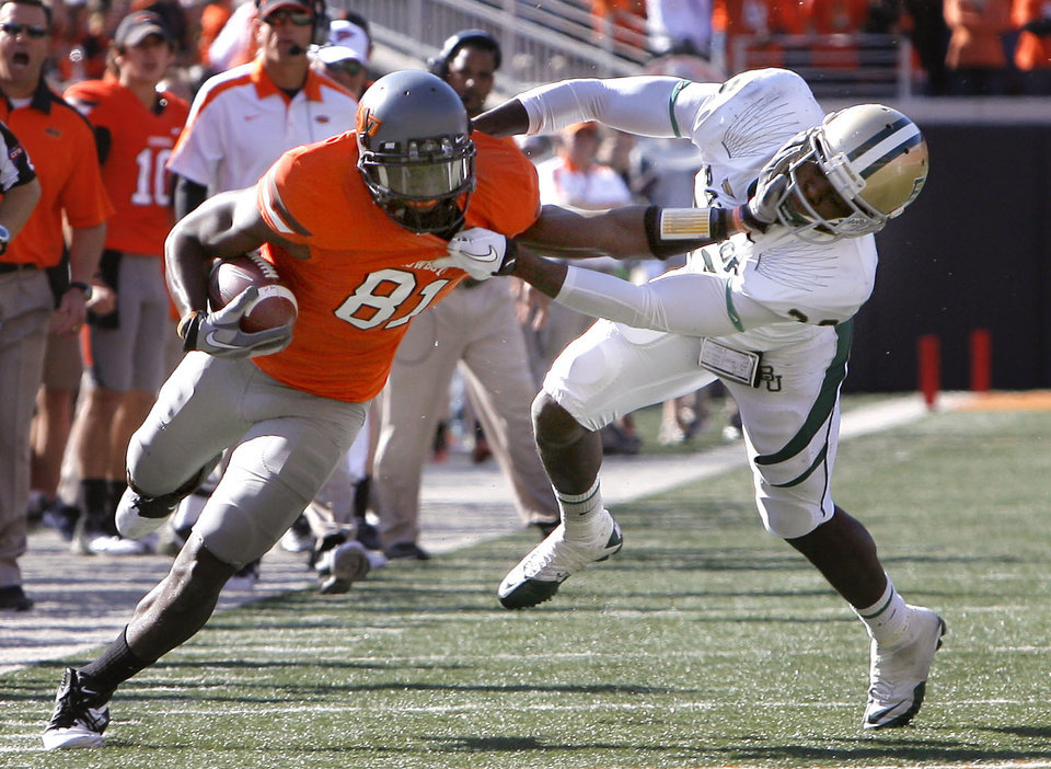 Photo - Oklahoma State's Justin Blackmon (81) stiff arms Baylor's Joe Williams (22)during a college football game between the Oklahoma State University Cowboys (OSU) and the Baylor University Bears (BU) at Boone Pickens Stadium in Stillwater, Okla., Saturday, Oct. 29, 2011. Photo by Sarah Phipps, The Oklahoman