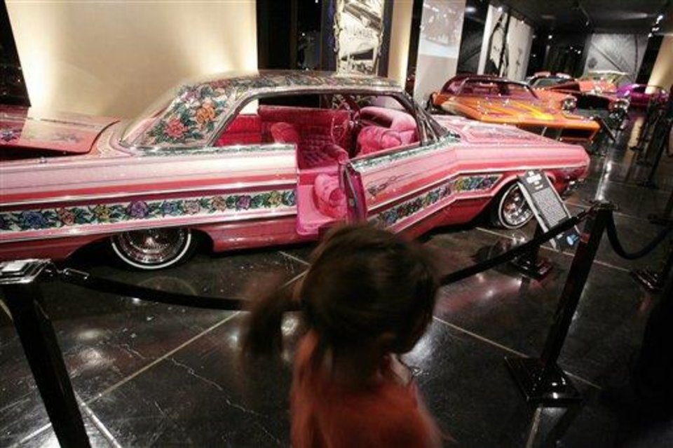"""FILE - In this Feb. 10, 2008 file photo, visitors to the Peterson Automobile Museum examine a 1964 Chevrolet Impala """"Gypsy Rose"""" lowrider in Los Angeles. She was a cover girl, had a bit part in a popular '70s TV show and was an icon of car culture. """"Gypsy Rose,"""" an award-winning Chevy Impala admired for its elaborate floral paint job, was known in the world of cruising low-riders as one of the most flamboyantly tricked-out muscle cars of a generation. On Saturday, the rose-covered ride will lead a funeral procession through East L.A., behind the hearse that carries its owner to his final resting place. (AP Photos/Ric Francis, File)"""