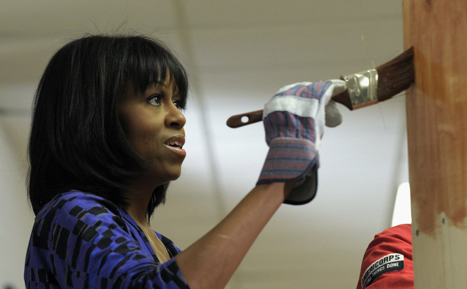 Photo - First lady Michelle Obama stains a bookshelf at Burrville Elementary School in Washington, Saturday, Jan. 19, 2013, as the first family participated in a community service project for the National Day of Service as part of the 57th Presidential Inauguration. (AP Photo/Susan Walsh)