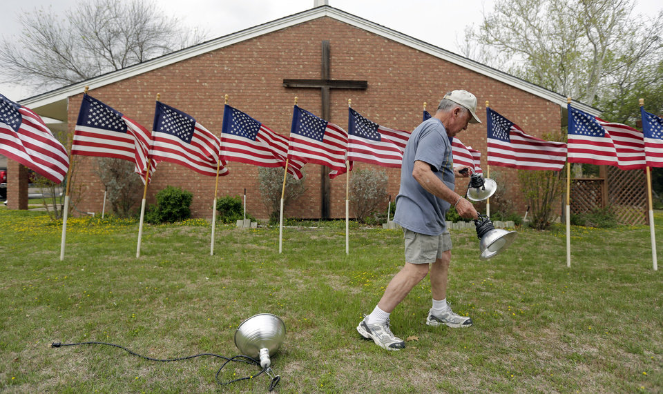 Photo - Bob Gordon works on a memorial for the victims of Wednesday's shooting at Fort Hood, Thursday, April 3, 2014, at Central Christian Church in Killeen, Texas. A soldier opened fire Wednesday on fellow service members at the Fort Hood military base, killing three people and wounding 16 before committing suicide. (AP Photo/Eric Gay)
