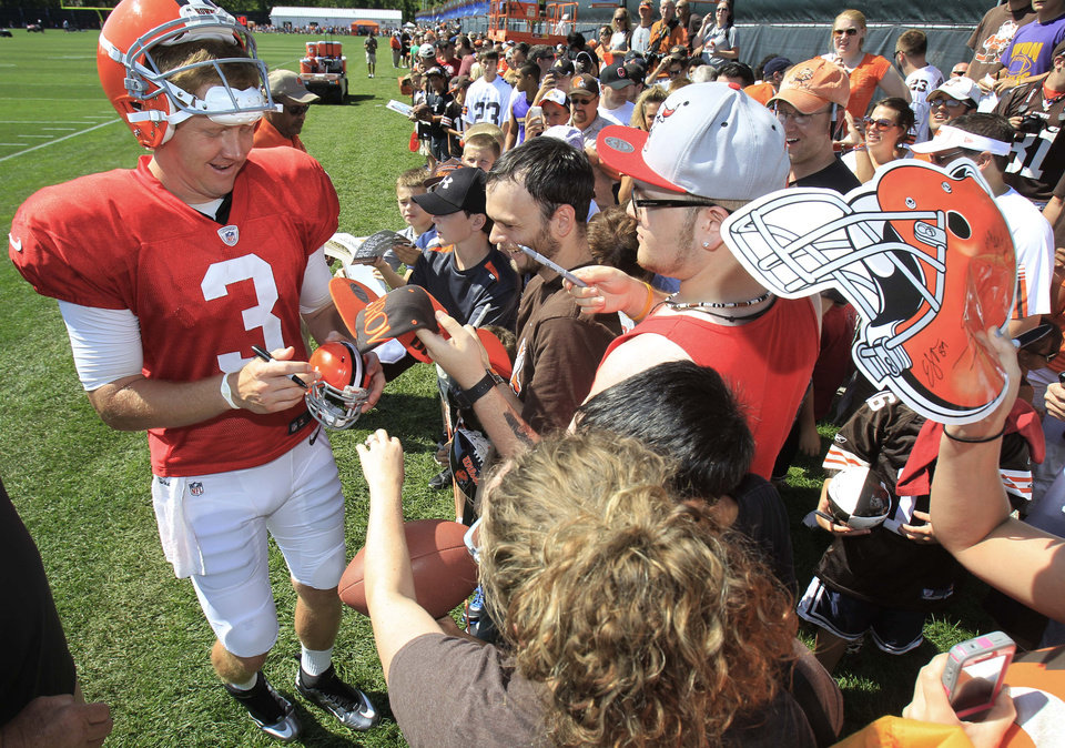Cleveland Browns quarterback Brandon Weeden signs autographs for fans after NFL football training camp on Sunday, July 29, 2012, in Berea, Ohio. (AP Photo/Tony Dejak) ORG XMIT: OHTD110
