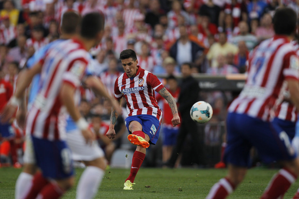 Atletico\'s Jose Sosa, centre, takes a shot on goal during a Spanish La Liga soccer match between Atletico Madrid and Malaga at the Vicente Calderon stadium in Madrid, Spain, Sunday May 11, 2014. (AP Photo/Gabriel Pecot)
