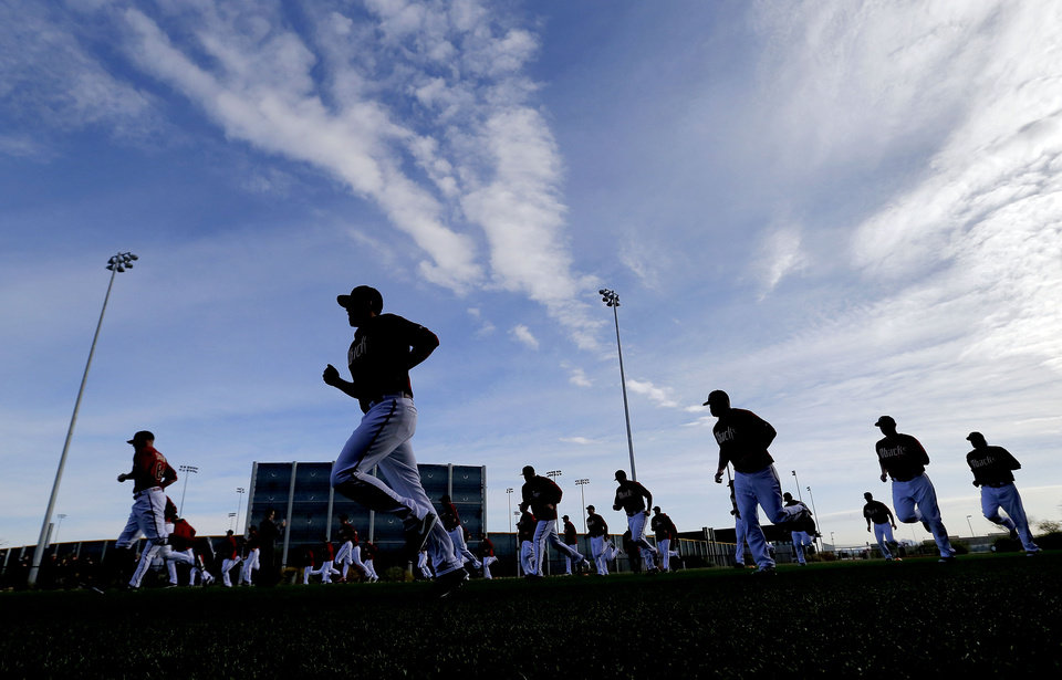 Photo - The Arizona Diamondbacks runs drills during the teams first baseball spring training workout, Friday, Feb. 7, 2014, in Scottsdale, Ariz. (AP Photo/Matt York)