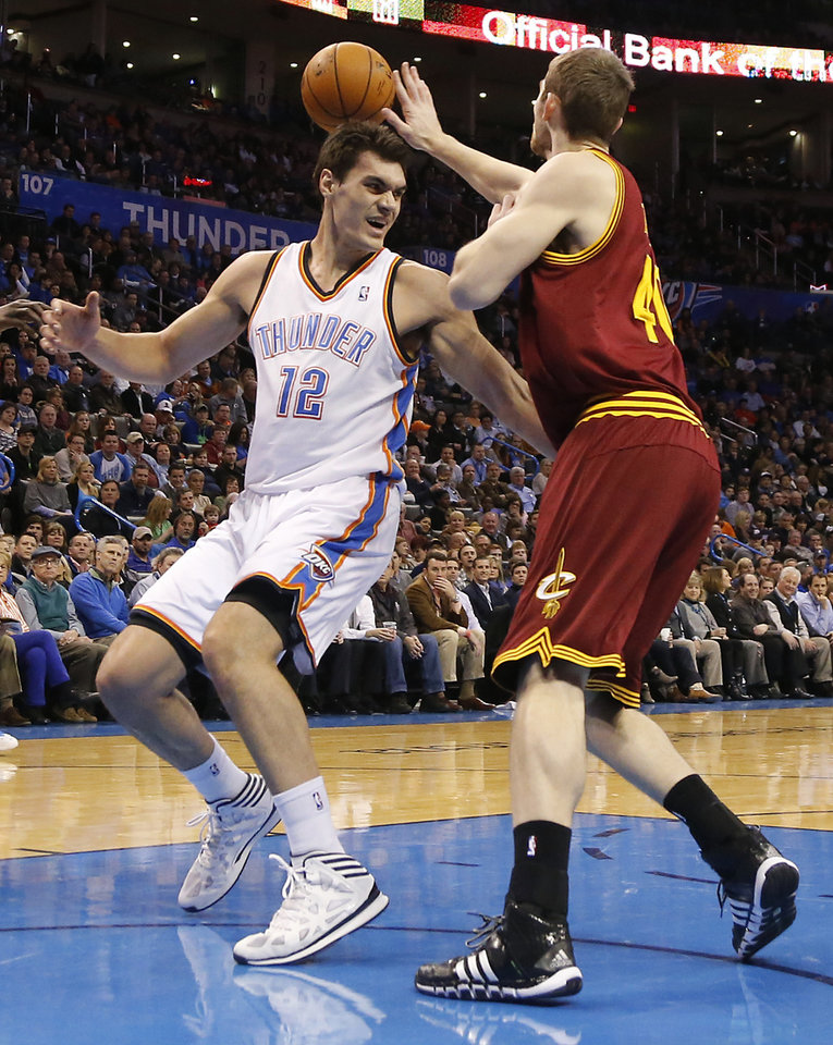 Photo - Oklahoma City's Steven Adams (12) looses the ball in front of Cleveland's Tyler Zeller (40) during the NBA basketball game between the Oklahoma City Thunder and the Cleveland Cavaliers at the Chesapeake Energy Arena in Oklahoma City, Okla. on Wednesday, Feb. 26, 2014.  Photo by Chris Landsberger, The Oklahoman