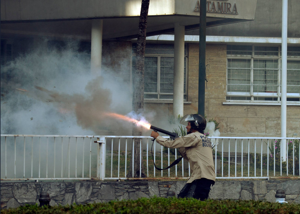 Photo - A Bolivarian National Police officer fires tear gas towards protesters in Caracas,Venezuela, Saturday, March 8, 2014. The Venezuelan government and opposition appear to have reached a stalemate, in which street protests continue almost daily while the opposition sits out a peace process it calls farcical. (AP Photo/Fernando Llano)