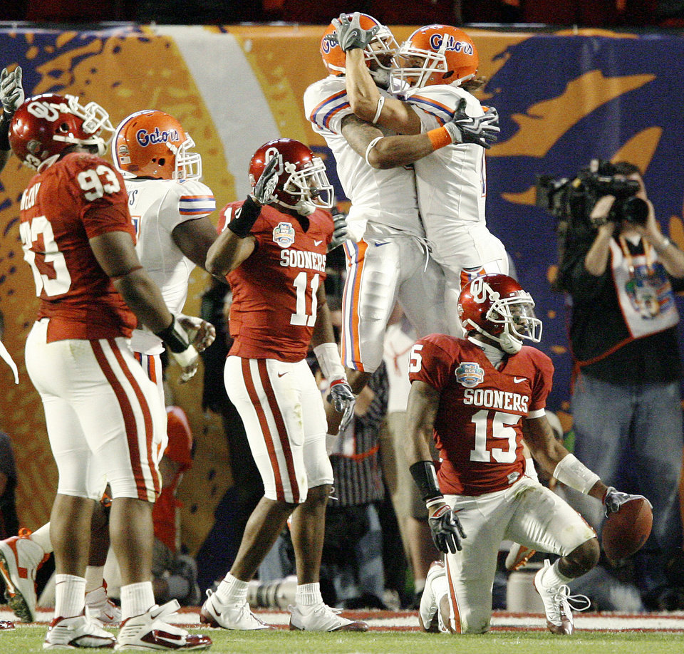 Photo - Florida's Louis Murphy, left, and Riley Cooper celebrate a touchdown behind OU's Lendy Holmes and Dominique Franks during the first half of the BCS National Championship college football game between the University of Oklahoma Sooners (OU) and the University of Florida Gators (UF) on Thursday, Jan. 8, 2009, at Dolphin Stadium in Miami Gardens, Fla. 