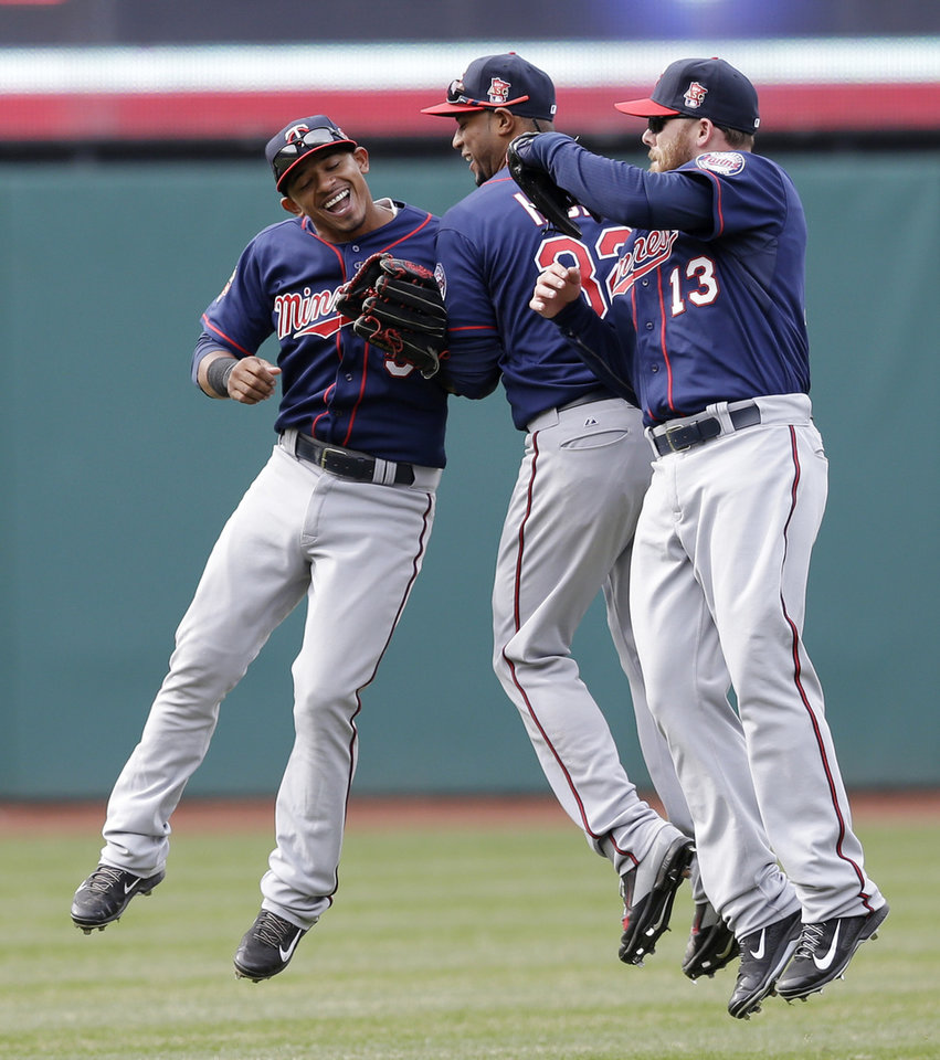 Photo - From left to right, Minnesota Twins' Eduardo Escobar, Aaron Hicks and Jason Kubel celebrate after they defeated the Cleveland Indians 10-7 in a baseball game, Sunday, April 6, 2014, in Cleveland. (AP Photo/Tony Dejak)