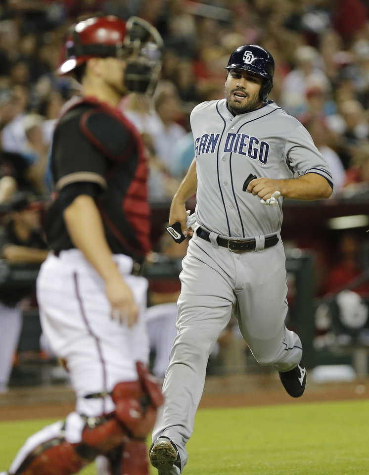 Photo - San Diego Padres' Carlos Quentin, right, scores on a single by teammate Yonder Alonso during the third inning of a baseball game against the Arizona Diamondbacks, Saturday, May 25, 2013, in Phoenix. Diamondbacks catcher Miguel Montero, left, looks on. (AP Photo/Matt York)
