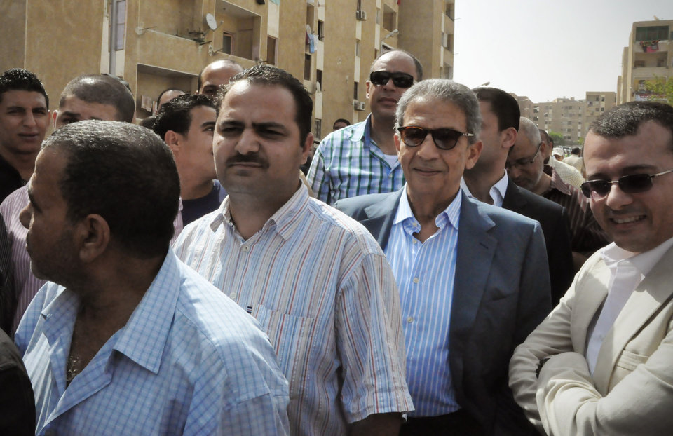 Photo -   In this photo provided by Amr Moussa's Campaign, Egyptian presidential candidate Amr Moussa, 2nd right, stands in line to cast his vote outside a polling center, in Cairo, Egypt, Wednesday, May 23, 2012. On Wednesday morning, Egypt commenced two days of presidential voting after 16 months of interim rule by the Supreme Council of Armed Forces. This election is the first free and fair race since the ouster of former President Hosni Mubarak. (AP Photo/Ahmed Almekdamy, Amr Moussa Campaign)