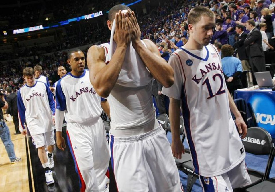 Photo -  NCAA TOURNAMENT / COLLEGE BASKETBALL: KU's Xavier Henry (1) covers his face as he leaves the court between Brady Morningstar (12), right, and  C.J. Henry (13) after the NCAA Men's basketball tournament second round game between the University of Kansas and the University of Northern Iowa at the Ford Center in Oklahoma City, Saturday, March 20, 2010. UNI upset KU, 69-67. Photo by Nate Billings, The Oklahoman ORG XMIT: KOD