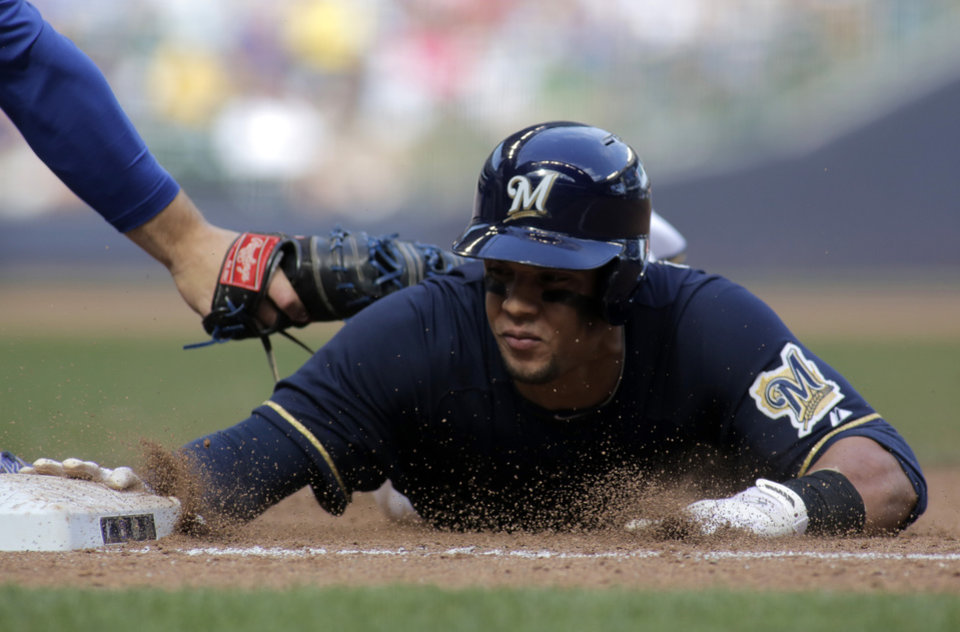 Photo - Milwaukee Brewers center fielder Carlos Gomez, right, safely slides back to first base against the Chicago Cubs during the fourth inning of a baseball game Saturday, May 31, 2014, in Milwaukee. (AP Photo/Darren Hauck)
