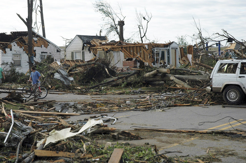 Photo - A man pauses to look at damage from a deadly tornado, on Thursday, April 28, 2011, in Tuscaloosa, Ala. The twister demolished a neighborhood and commercial area near the University of Alabama. (AP Photo/Jay Reeves)