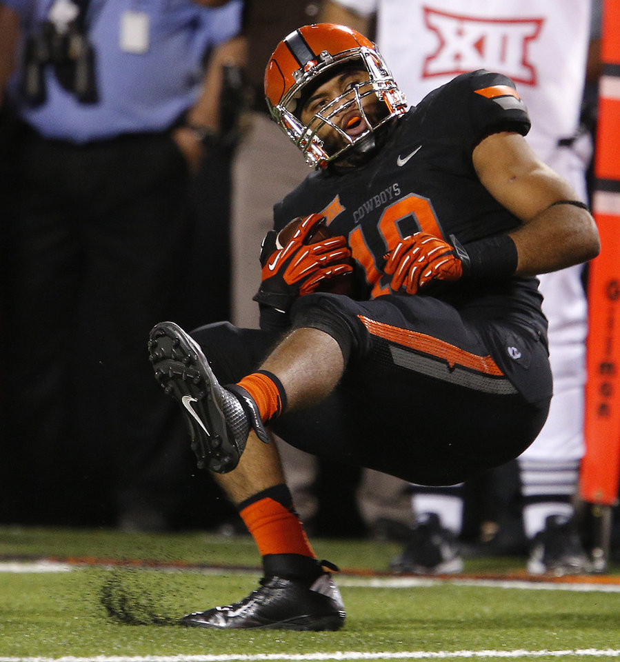 Photo - Oklahoma State's Seth Jacobs (10) intercepts a pass during a college football game between the Oklahoma State Cowboys (OSU) and the Texas Tech Red Raiders at Boone Pickens Stadium in Stillwater, Okla., Thursday, Sept. 25, 2014. Photo by Bryan Terry, The Oklahoman